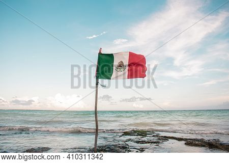 Mexican Flag Waving On A Hillside Pole Embedded In The Shore Of The Beach With Background Of The Sea