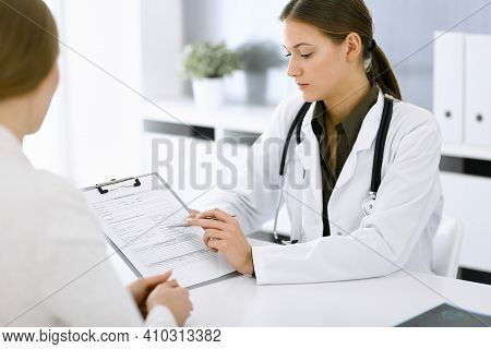 Woman-doctor And Patient Sitting And Talking At Hospital Office. Green Color Blouse Suits To Therapi
