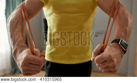Close-up Shot Of A Man Exercising At Home With An Elastic Band. Man In A T-shirt And Strong Arms Is