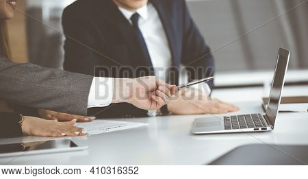 Unknown Businessmen And Woman Sitting, Using Laptop Computer And Discussing Questions At Meeting In