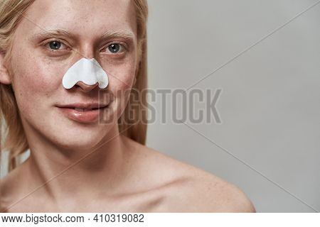 Portrait Of Handsome Young Caucasian Boy With Long Fair Hair Using Nose Pore Cleansing Strips And Sm