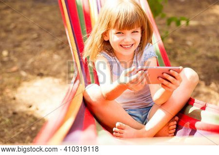 Smiling Child Girl Recording Lifestyle Blog Talking To Camera Of Mobile Phone Outdoor, Sitting On Ha