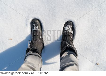 Top View Of Black Boots Standing In The Snow