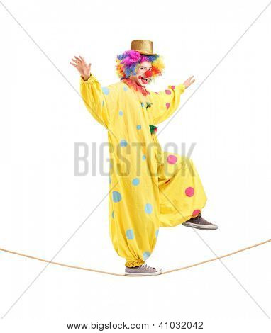 Full length portrait of a happy male clown walking on a rope isolated on white background