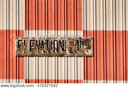 Weathered elevation sign on an old hangar wall.