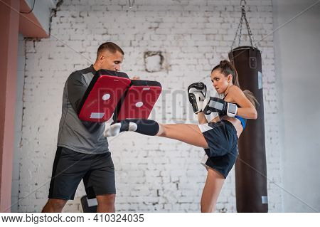 Female Martial Arts Fighter Practicing Leg Kick Or High Kick With Her Trainer In A Boxing Studio At