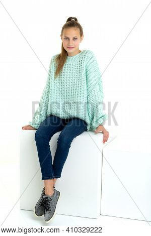 Cheerful Teen Girl Sitting On White Cube In Studio. Beautiful Girl With Ponytail Wearing Fashionable