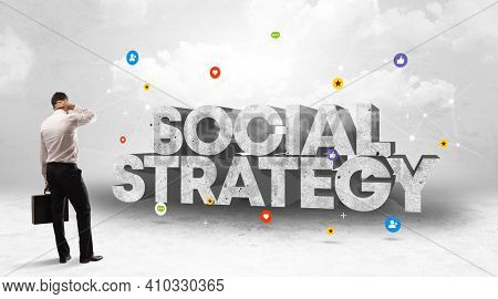 Young businessman standing in front of SOCIAL STRATEGY inscription, social media concept