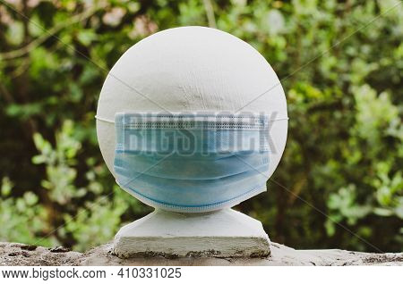 Medical Mask On A Round Fence Decoration In The Garden In Nature. Material Contrast Concept