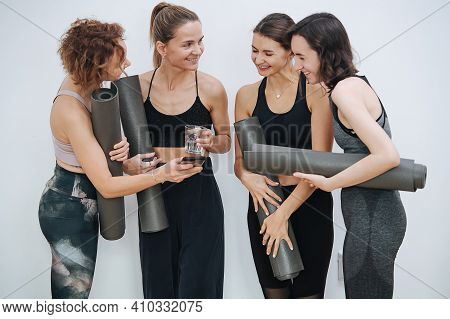 Group Of Friendly Women Socialising At Yoga Club, Holding Rolled Mats Under Arm