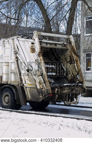 The Back Of A White Garbage Truck Taking Out Garbage In The City In Winter