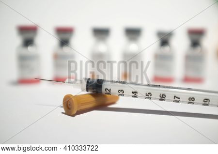 Uncovered Syringe And Vaccine Ampules Or Glass Vials. Selective Focus. Isolated Over White