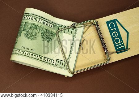 Mousetrap With Money. Dollars And The Inscription: Credit. Brown Background. Wooden Mousetrap