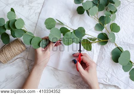 Florist Hands Make Eucalyptus Bouquet. Florist Workplace Background. Eucalyptus Branches, Tools Set