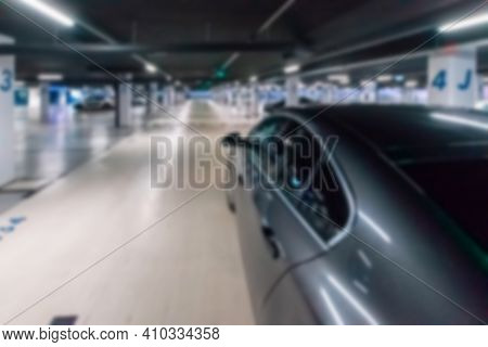 Rent Parking Space Blurred. Car Lot Parking Space In Underground City Garage. Empty Road Asphalt Bac