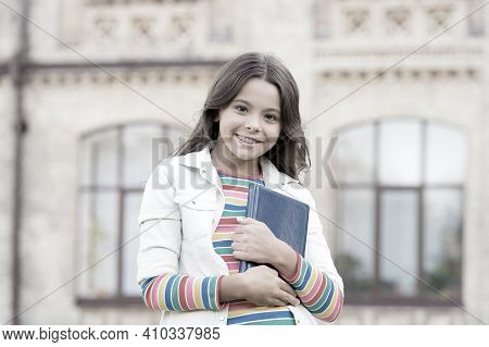 She Seems To Know Everything. Smart Girl Hold Book Outdoors. Happy Girl Back To School. Primary Scho