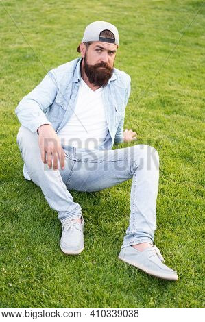 Stylish And Comfortable To Wear. Stylish Hipster In Baseball Cap Sitting On Green Grass Outdoor. Bea