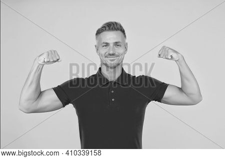 Strong Athletic Guy Smile In Red Tshirt Flexing Muscular Arms Yellow Background, Strength.