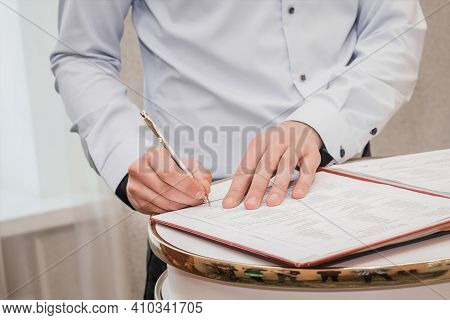 The Hands Of The Witness's Boyfriend In The Shirt Put The Signature On The Wedding Close-up.
