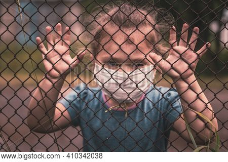 A Child In A Medical Mask Holds The Fence With His Hands.