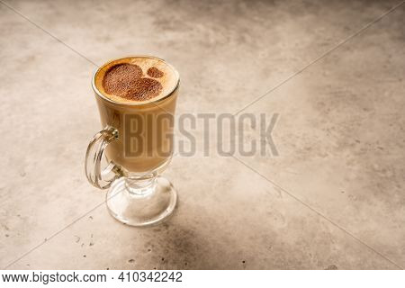 A Tall Glass Cup Of Coffee With Hearts Painted On It. Latte Macchiato On Background. Copy Space For
