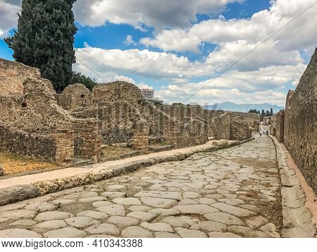 Empty Ancient Roman City Of Pompeii Under A Blue Sky With Clouds. Panorama Of An Abandoned Street In