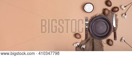 Horizontal Banner With Ceramic Plate On Burlap Cloth With Easter Eggs, Cream Bowl And Cotton Flowers