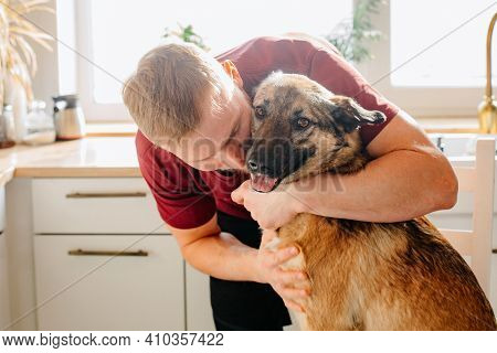 A Man Of European Appearance Hugs A Large Dog At Home. Love For Pets And Dogs