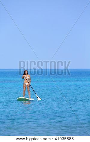Hawaii beach lifestyle woman paddleboarding in bikini. Beautiful multiethnic woman surfing on stand up paddleboard on Big Island, Hawaii.