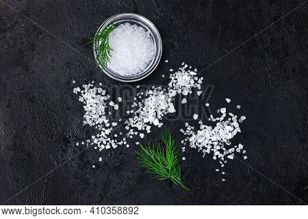 Coarse Salt Crystals On A Black Table. Bowl With Sea Salt. Background For Advertising Salty.