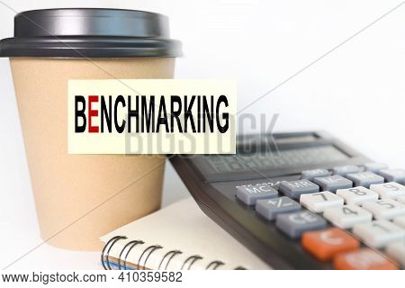 Benchmarking Concept. Text On Yellow Sticker. Sticker Pasted On A Cup Of Coffee On A White Backgroun