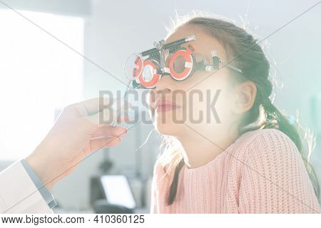 Elementary schoolgirl sitting in front of ophthalmologist or optometrist during check-up of her eyesight with special eyeglasses in clinics