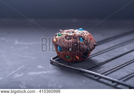 Chocolate Cupcake With Colored Chocolates On A Dark Background. Cupcake And Kitchen Baking Rack. Fro