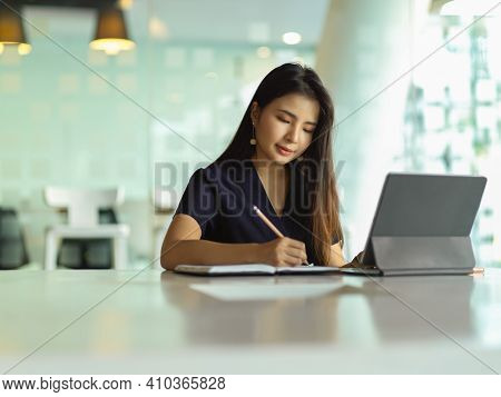 Businesswoman Hand Writing On Notebook While Working With Laptop On The Table