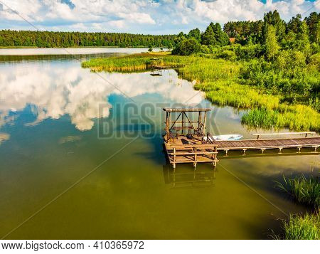 Green Summer Landscape In Europe. Wooden Jetty On Shore Of Lake Kierwik In Masuria Poland. Blue Sky