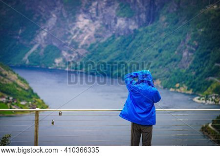 Tourist Person With Camera Taking Travel Picture From Fjord Geirangerfjord, Flydasjuvet Viewing Poin