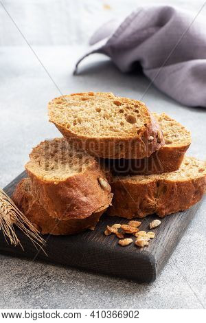 Sliced Rye Baguette On A Gray Background With Cereals. Whole Grain Bread, A Healthy Food Concept. Co