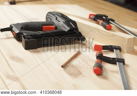 Iron Clamps. Electric Stapler. On A Wooden Table. Clamping Tools.