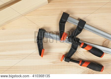 Iron Clamps On A Wooden Table. Clamping Tools.