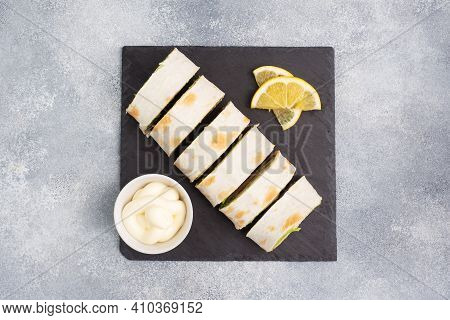 Rolls Of Thin Pita Bread And Red Salted Salmon With Lettuce Leaves On A Slate Stand, Grey Concrete B