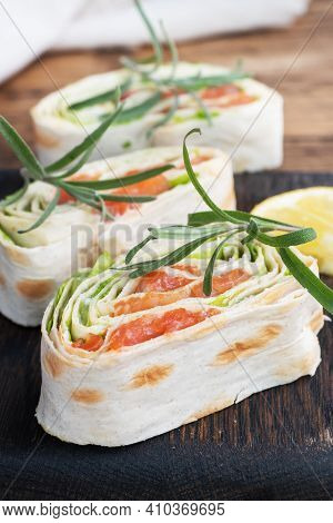 Rolls Of Thin Pita Bread And Red Salted Salmon With Lettuce Leaves On A Wooden Cutting Board.