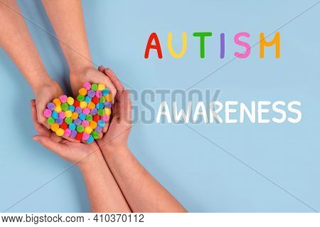 World Autism Awareness Day Concept - Autistic Child's Hands Supported By Mother Holding Multicolored