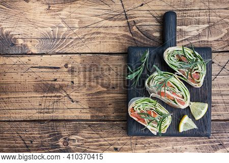 Rolls Of Thin Pita Bread And Red Salted Salmon With Lettuce Leaves On A Wooden Cutting Board. Copy S