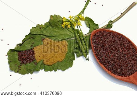 Black Mustard Seeds In Wooden Ladle With Mustard Sauce On Leaf Isolated On White Background