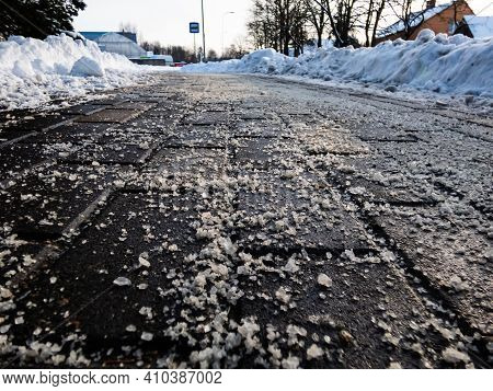 Salt Grains On Icy Sidewalk Surface In The Winter. Applying Salt To Keep Roads Clear And People Safe