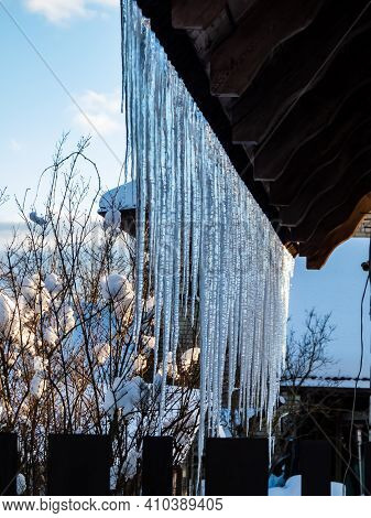 Icicles Hanging From Rooftop Covered With A Lot Of Snow