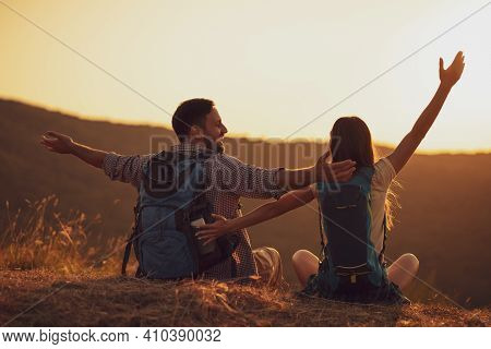 Young Happy Couple Is Hiking In Mountain And Looking At Sunset.