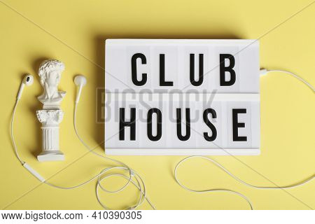 White Headphones With Small Statue And Lightbox With Text Clubhouse On Yellow Background. Top View F