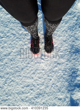 Woman Standing In Running Tights And Shoes In Snow Ready To Start Running. Athlete Woman Runner In W