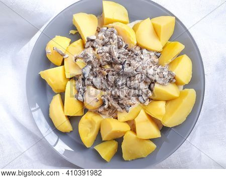 Boiled Potatoes With Mushroom Creamy Sauce From Various Kinds Of Mushrooms On Grey Plate On White Ta